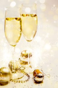 Two champagne glasses and cork with baubles, sparklers, confetti and lights. Copy space.